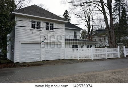 WEQUETONSING, MICHIGAN / UNITED STATES - DECEMBER 22, 2015: A white home with an attached two-door garage on Beach Road in Wequetonsing, Michigan.