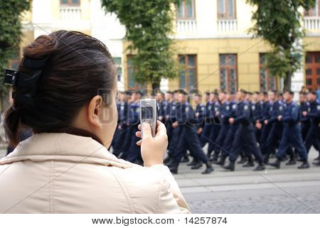 A girl takes pictures soldiers on a city parade