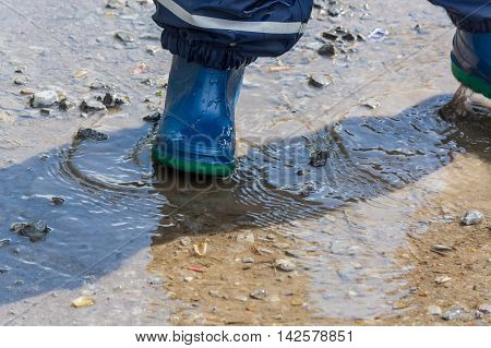 Child with blue rubber boots in a puddle. close up view
