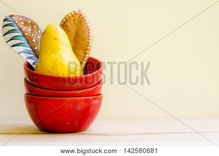 Trio of red bowls, two painted leaves and one pear.