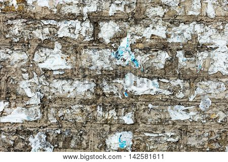 Texture of old brick wall with scraps of burnt paper on it