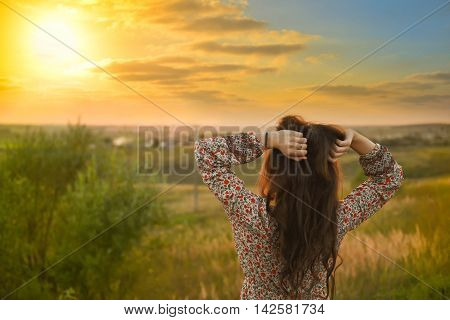 Beauty Girl Outdoors enjoying nature. Beautiful Model girl with long healthy blowing hair running on the Spring Field, Sun Light. Glow Sun. Free Woman. Toned in warm colors.