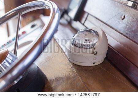 White compass on old ship next to a metal steering wheel closeup