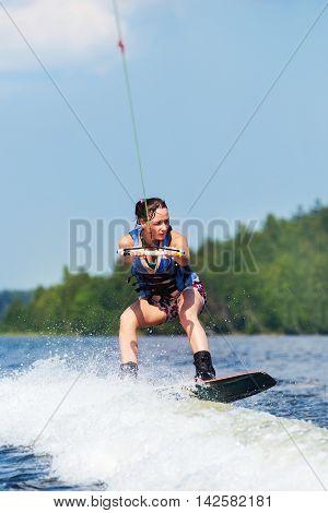 Slim Brunette Woman Riding Wakeboard On Motorboat Wave In Lake