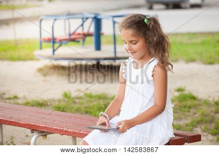 Cute little girl is using tablet while walking. technology and internet concept