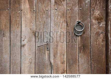handle and knocker on weathered wooden door, Serbia
