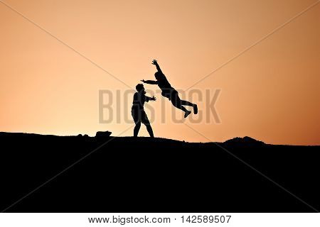 A Silhouette Of A Guy Catches His Girl Jumping On Him With Open Arms