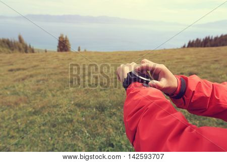 hiker checking the altimeter on sports watch at mountain peak