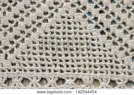 Handmade crocheted cotton organic blanket on wooden background