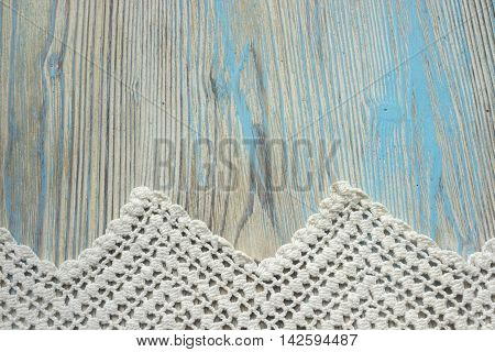 Handmade crocheted cotton organic blanket on wooden background