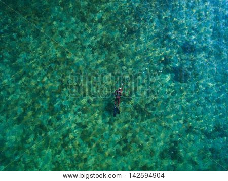 spearfishing freediver under water with a bird's-eye view