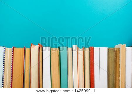 Colorful composition with vintage old hardback books, diary on wooden deck table and blue background. Books stacking. Back to school. Copy Space. Education background
