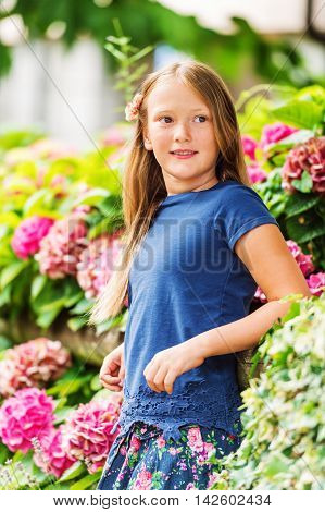 Outdoor vertical portrait of a cute little girl of 9 years old in summer garden, leaning on a fence, wearing blue tee shirt