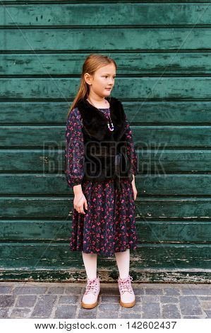 Outdoor fashion portrait of a cute little girl of 8 years old, wearing black dress and faux fur coat, standing next to green wooden wall