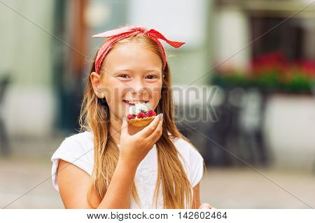 Funny little girl eating cake outdoors, wearing red polka dot head band