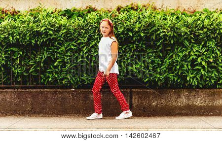 Outdoor fashion portrait of a ute little girl of 8-9 years old walking down the street, wearing polkadot trousers and white tee shirt, toned image