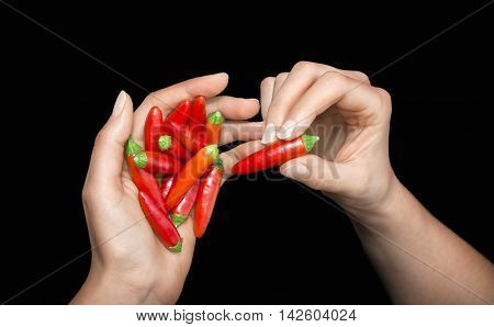 Red hot chili pepper in  woman's hands on a black background