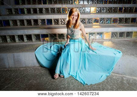 A beautiful blond teen girl sits in front of glass block admiring her prom dress which is spread out around her. She looks like a princess.