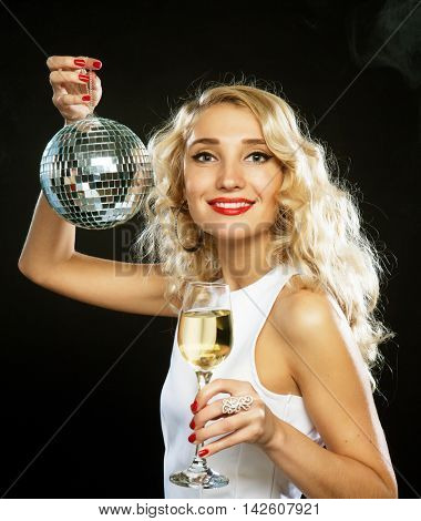 beautiful blond woman in evening dress with wine and disco ball