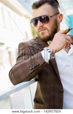 Handsome man in sunglasses and with cigarette in his hand
