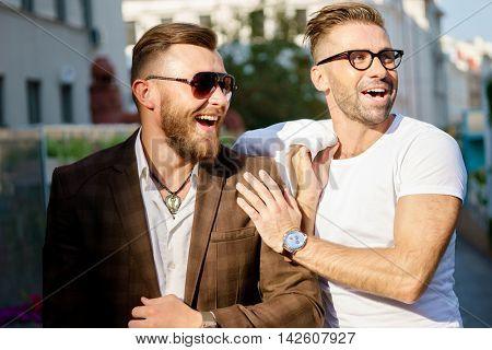 Two elegant smiling bearded men on street background
