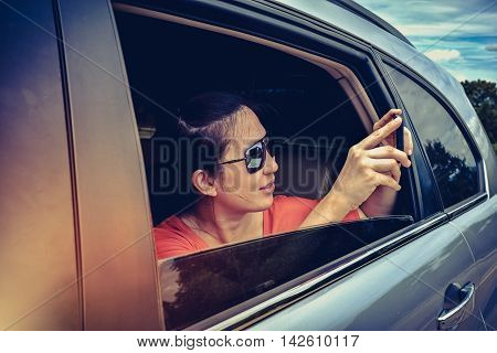 High contrast of happy asian woman holding mobile phone and taking photos in the car. Traveler capturing a perfect road trip moment on travel vacation. Outdoor at the daytime with bright sunlight.