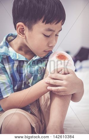 Child Injured. Wound On The Child's Knee With Bandage. Vintage Tone Effect.