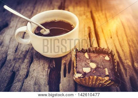 Cake Chocolate Brownie And Hot Coffee On Old Wooden Background. High Contrast.