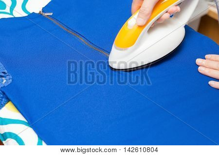 woman ironing clothes on ironing board horiozontal