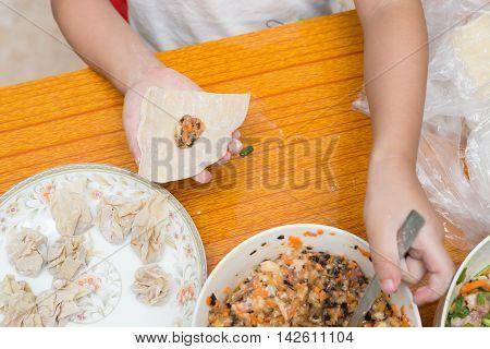 boy making wontons at home horizontal composition