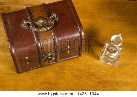 Old treasure chest and an inkwell on a wooden background