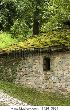 Old country stone house with stone roof slabs overgrown with green moss on forest background