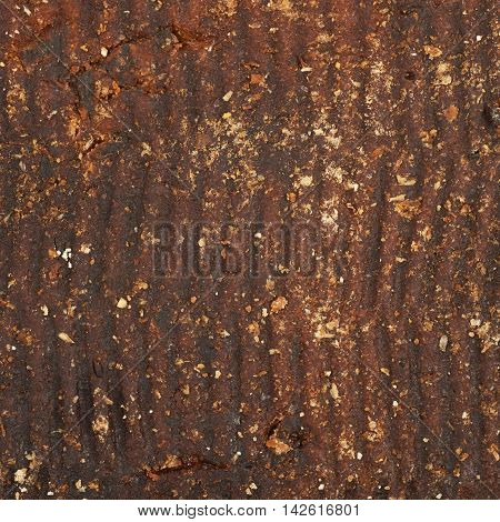 Fragment of a brown bread crust as a background texture composition