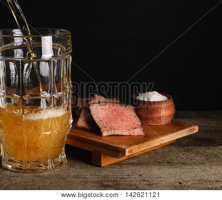 Beer poured into glass close up on dark background. Lager beer with meat snack to beer