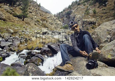 Young photographer Aleem Zahid Khan hiking Sitting on rock and tying his shoes in the mountains near waterfall