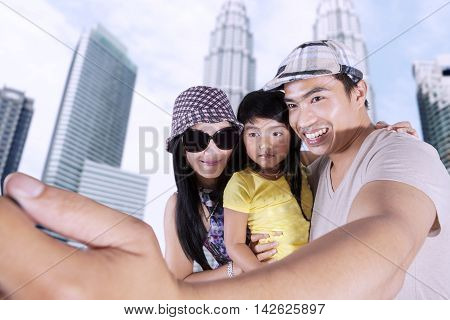 Happy Asian family enjoying holiday while taking selfie photo together near the skyscraper building