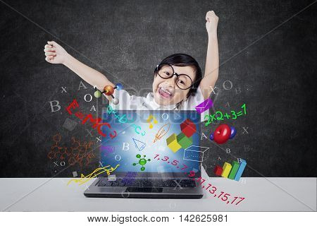 Cheerful female elementary school student raising hands in the class with formula of science math and physics on the laptop screen