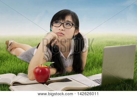 Picture of a beautiful high school student lying on the meadow while studying with book and daydreaming