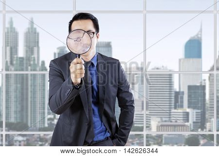 Young businessman looking through a magnifying glass in the office