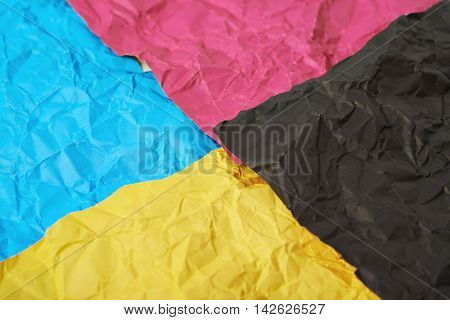Four CMYK colored crumpled origami paper sheets as an abstract backdrop composition