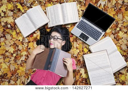 Portrait of female college student sleeping on the autumn leaves while holding a textbook