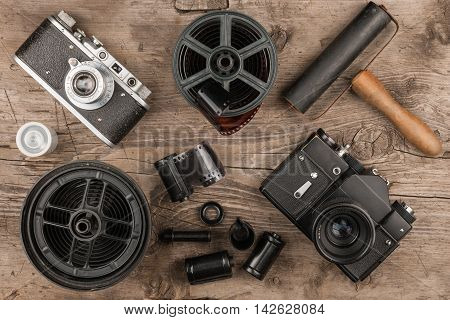Old cameras developing tank tapes film and roller for photos top view