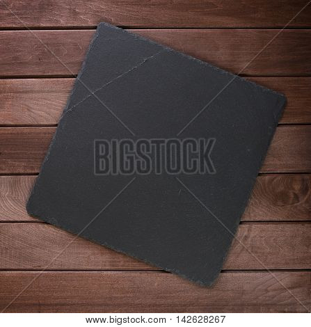 stone slate board with copy space on rustic wooden background