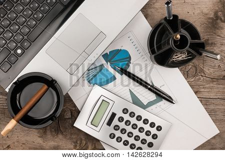 Working businessman desk laptop cigar and diagram as the background view from above