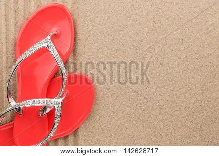 Beach red flip flops encrusted with rhinestones standing on the sand with space for your text