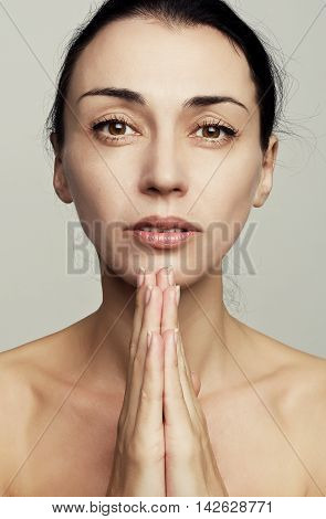 Beautiful brunette woman clenches hands to pray