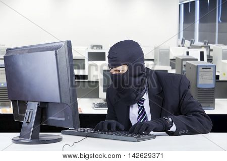 Photo of a male burglar wearing mask and steal data on the computer shot in the office
