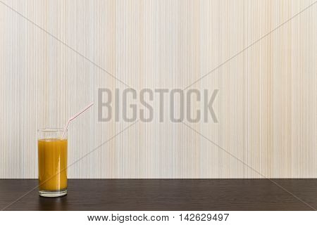 Glass of juice with straw on a wooden surface wenge color on the background wall with texture in a vertical strip. Minimalism. Background with copy space.