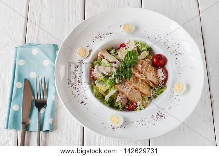 Warm salad with chicken and toasts on white wooden table, served with knife and fork on blue napkin. Healthy food, restaurant serving, regale