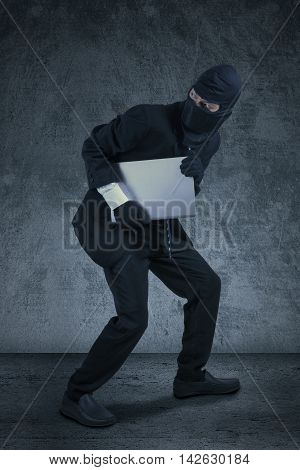 Male robber wearing mask and stealing a notebook computer while skulking
